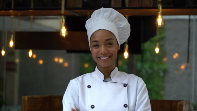 beautiful black female chef smiling at camera with arms crossed - chef stock videos & royalty-free footage