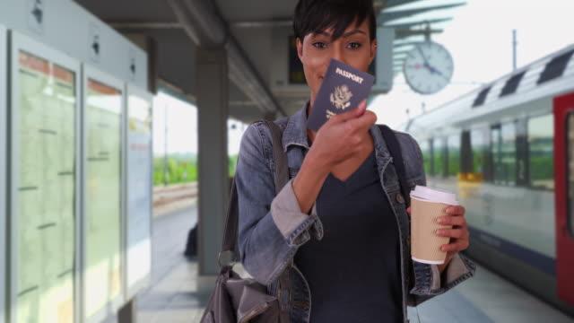 vidéos et rushes de beautiful black female drinking coffee at train station finds missing passport - être perdu