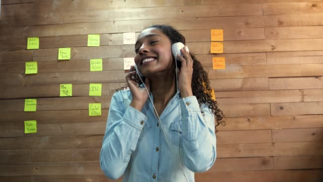 beautiful black female woman relaxing at the office putting her headphones on looking very happy - headphones stock videos & royalty-free footage