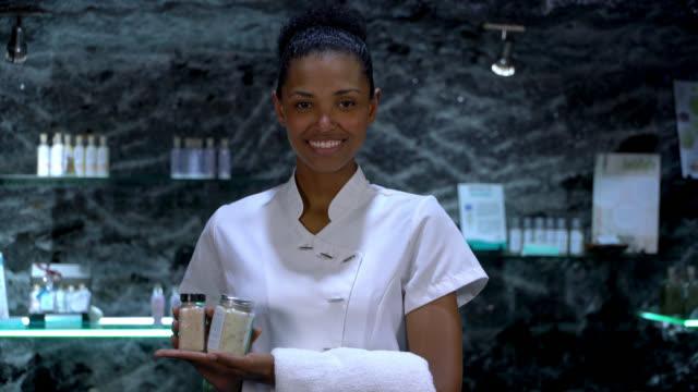 vídeos y material grabado en eventos de stock de hermosa vendedora negra en un spa que sostiene productos y una toalla mientras se enfrenta a la cámara sonriendo - tratamiento de spa