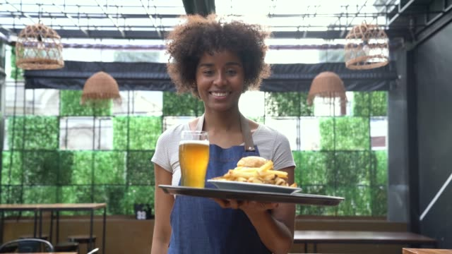 Beautiful black waitress taking an order ro customer on tray while facing camera smiling