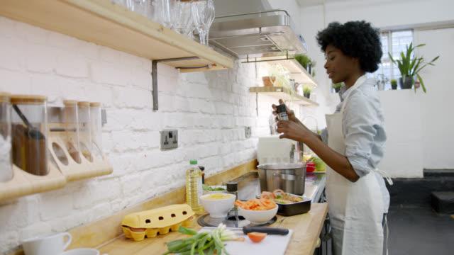 vídeos de stock e filmes b-roll de beautiful black woman at home preparing a delicious meal on stove - domestic kitchen