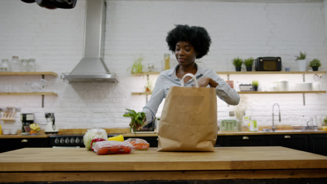 beautiful black woman at home unpacking her groceries and smelling a vegetable looking very happy - paper bag stock videos & royalty-free footage