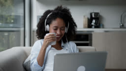 Beautiful black woman at home watching a movie on laptop wearing headphones and enjoying a hot chocolate