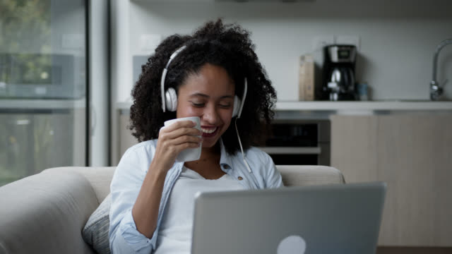 beautiful black woman at home watching a movie on laptop wearing headphones and enjoying a hot chocolate - tea hot drink stock videos & royalty-free footage