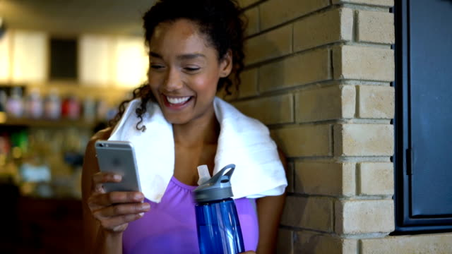 Beautiful black woman chatting on her smartphone after doing a workout at the gym