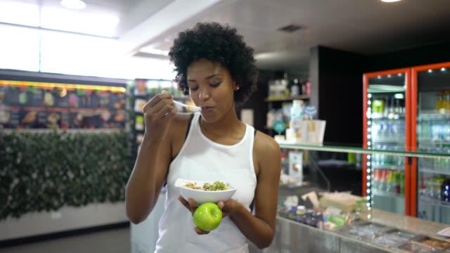vidéos et rushes de belle femme noire appréciant un bol de céréales avec des fruits après s'être travaillée dehors à la gymnastique - anatomie