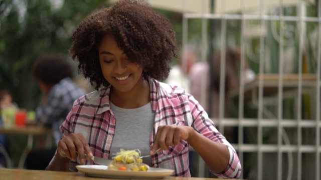 beautiful black woman enjoying a delicious meal at a restaurant - happy meal stock videos & royalty-free footage