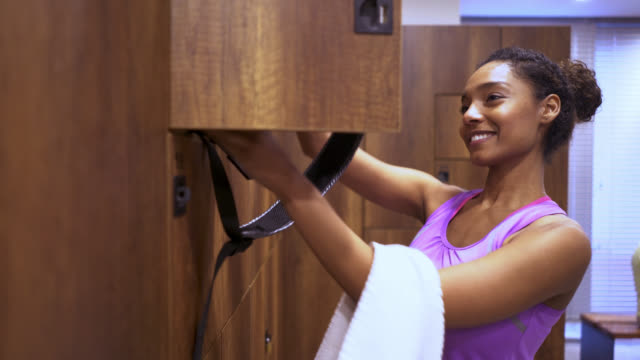 Beautiful black woman entering the locker room at the gym