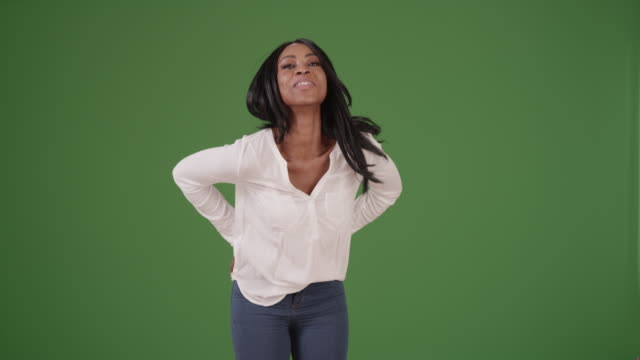 Beautiful black woman flirting with the camera in a blouse on green screen