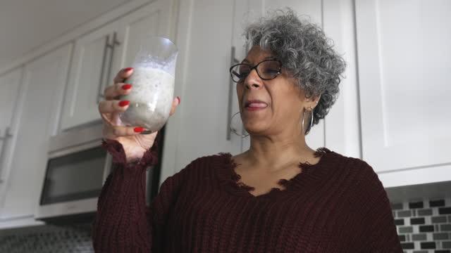 vídeos de stock, filmes e b-roll de linda mulher negra tomando um smoothie - satisfação