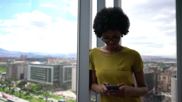 vídeos de stock, filmes e b-roll de mulher preta bonita que inclina-se no indicador ao texting no sorriso do smartphone - roupa descontraída