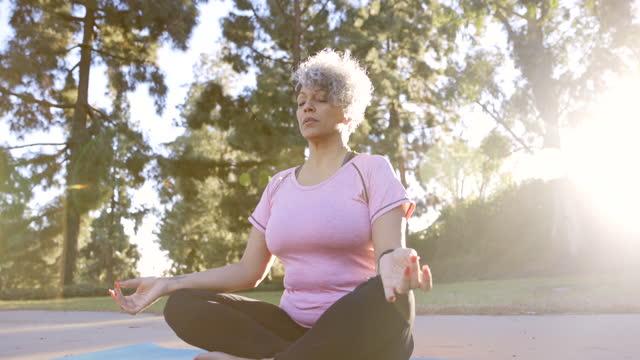 beautiful black woman meditating yoga - grey hair stock videos & royalty-free footage
