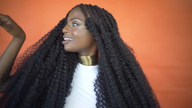 a beautiful black woman on an orange background. - halsreif stock-videos und b-roll-filmmaterial