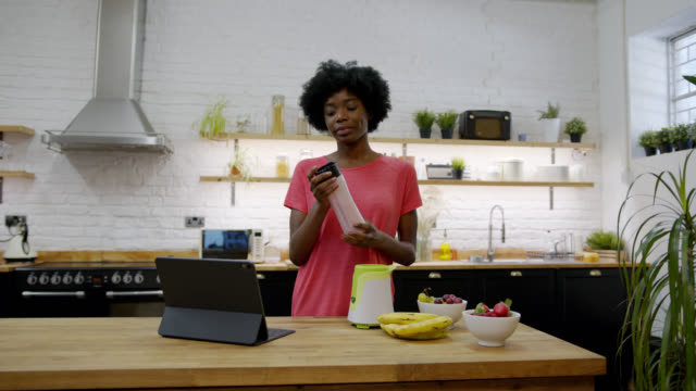 beautiful black woman preparing a smoothie following an online recipe on tablet - following moving activity stock videos & royalty-free footage