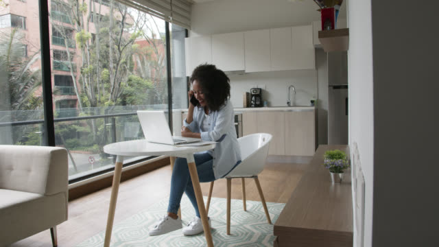 beautiful black woman receiving a phone call while working on laptop at home looking very happy - home interior stock videos & royalty-free footage