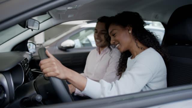 vídeos de stock, filmes e b-roll de bela mulher negra sentada no interior de um carro enquanto vendedor explica todas as propriedades segurando uma prancheta - new