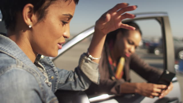 beautiful black woman talking to her best friend while hanging out in parking lot - african american culture stock videos & royalty-free footage