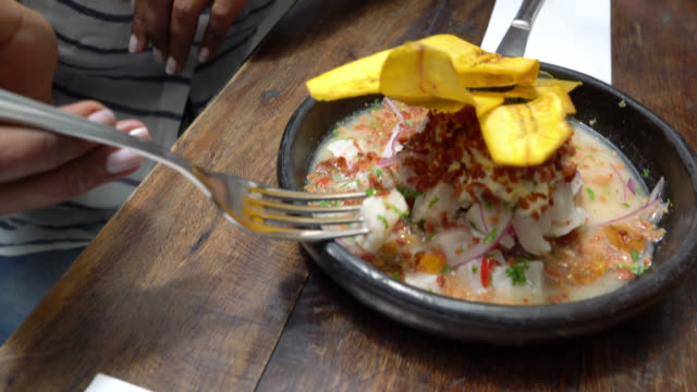 vídeos de stock e filmes b-roll de beautiful black woman trying out a ceviche with her male friend - marisco