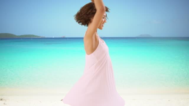 beautiful black woman twirling in white dress on caribbean beach.  happy woman spinning on white sandy beach. - vestito bianco video stock e b–roll