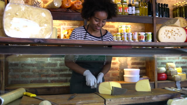 beautiful black woman working at a deli cutting a piece of cheese and then smiling at camera - grocer stock videos & royalty-free footage