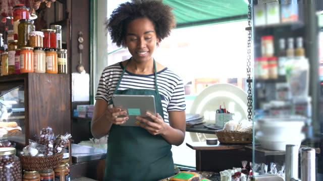 stockvideo's en b-roll-footage met mooie zwarte vrouw die bij een delicatessen werkt die peinzend wegkijkt terwijl het houden van een tablet - winkeldisplay