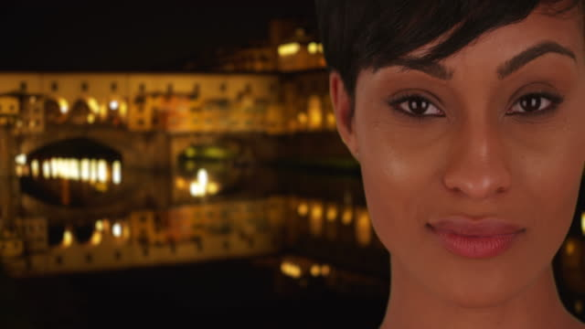 beautiful black young lady stares deeply at camera in florence at night - ponte stock videos & royalty-free footage