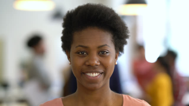beautiful black young woman at the office looking at the camera smiling - image focus technique stock videos & royalty-free footage