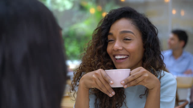 beautiful black young woman enjoying a hot chocolate while talking and laughing with a friend - enjoyment stock videos & royalty-free footage