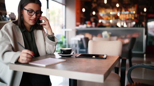 vídeos de stock, filmes e b-roll de o blogger bonito está escrevendo um artigo em um portátil no café - sentando
