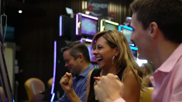 beautiful blond woman celebrating a win on slot machines at the casino and man sitting next to her celebrating too - casino winner stock videos & royalty-free footage