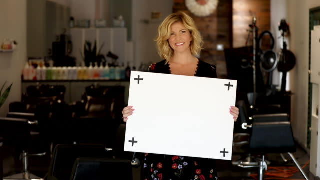 beautiful blond woman holds blank white sign in trendy hair salon - holding stock videos & royalty-free footage