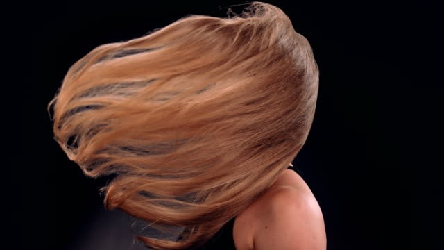 Beautiful blond woman tossing her long hair