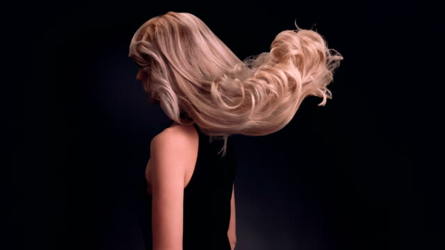 beautiful blond woman tossing her long, wavy hair - shampoo per capelli video stock e b–roll