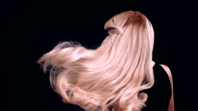 Beautiful blond woman tossing long hair. Waves
