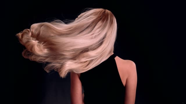 beautiful blond woman tossing long hair. waves - hair straighteners stock videos and b-roll footage