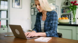 Beautiful Blond Woman Typing On Laptop At Kitchen Table