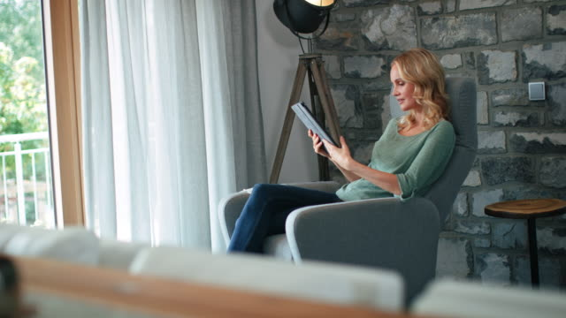 beautiful blond woman using digital tablet at home - comfortable stock videos & royalty-free footage