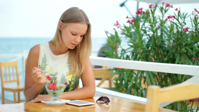 Beautiful blond young woman eating ice-cream, reading e-reader