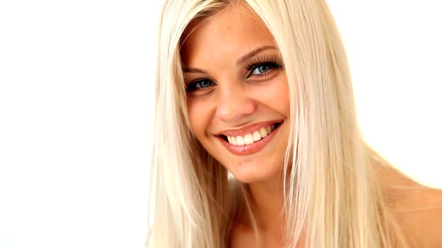 Schöne blonde Mädchen lächelt in die Kamera.