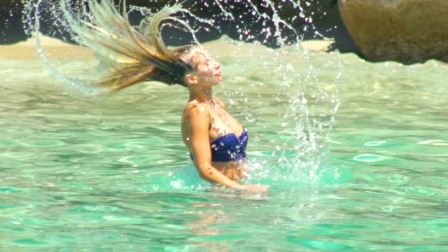 Beautiful blonde girl swimming in a clear water