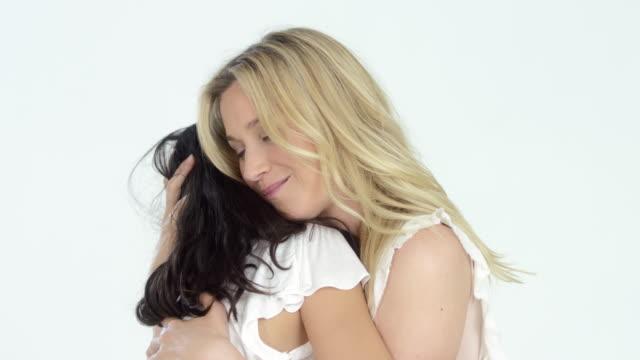 stockvideo's en b-roll-footage met beautiful blonde haired mother with her cute dark haired daughter - hugging and having fun - eskimokus geven