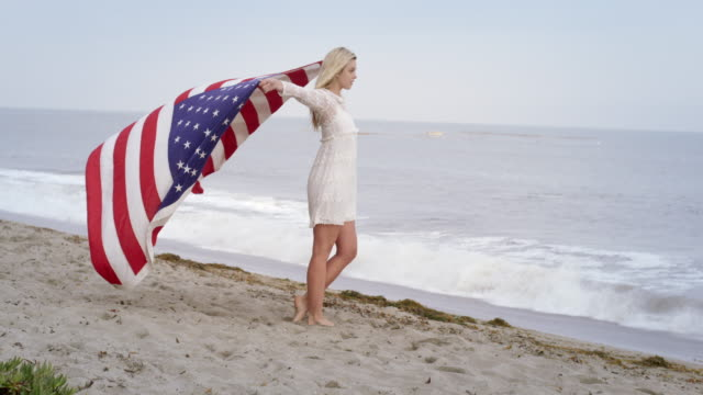 beautiful blonde holds up united states flag at the beach 4k - vesper stock stock videos & royalty-free footage