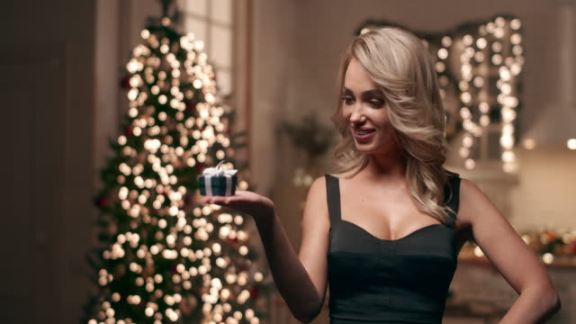 a beautiful blonde in an evening dress looks at her gift on the background of a christmas tree. - blonde hair stock videos & royalty-free footage