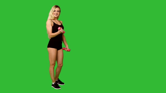 schöne blondine in der sportswear mit hanteln auf grünem hintergrund - handzeichen stock-videos und b-roll-filmmaterial