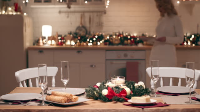 a beautiful blonde is preparing for the arrival of guests for christmas dinner. she sets a festive table in the kitchen in her house. - table stock videos & royalty-free footage