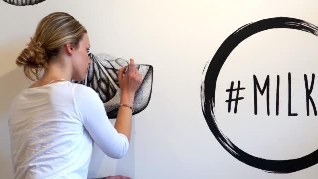 vídeos y material grabado en eventos de stock de hermosa artista mural rubia que duele una pieza de arte en una pared - dibujar