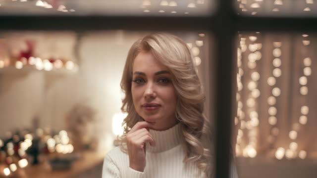 vídeos y material grabado en eventos de stock de una hermosa rubia en la víspera de navidad se encuentra en la ventana sobre el fondo de la cocina decorada con luces de navidad y mira a la calle. - imagen virada
