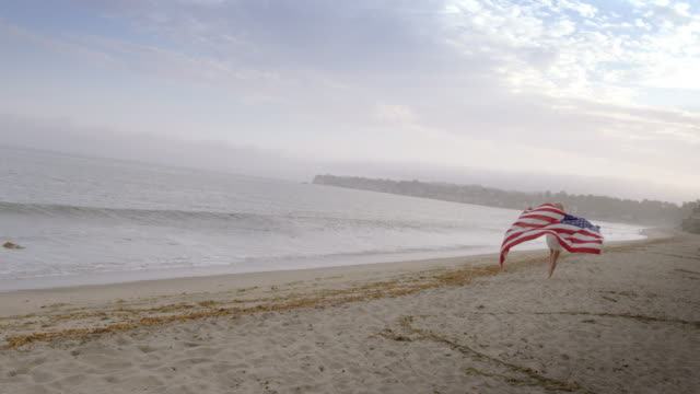 beautiful blonde running along california beach with united states flag 4k - vesper stock stock videos & royalty-free footage