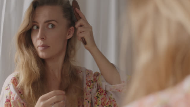 cu beautiful blonde woman brushes her hair in front of a mirror - body care stock videos & royalty-free footage